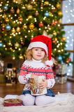 Little girl in red santa hat holding christmas gift box Stock Photos