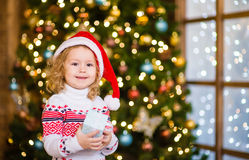 Little girl in red santa hat holding gift box Royalty Free Stock Photography
