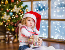 Little girl in red santa hat opening Christmas gifts Royalty Free Stock Images