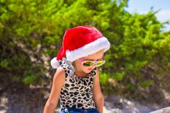 Little girl in red Santa hat on white beach Royalty Free Stock Photos