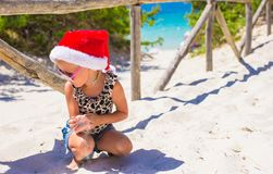 Little girl in red Santa hat on white beach Stock Image