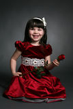 Little girl with red satin dress and a rose. Dark haired little girl in red dress with rose Royalty Free Stock Photos