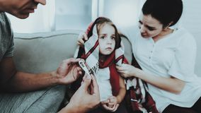 Little Girl in Red Scarf with Cold with Family. Sick Young Girl. White Sofa in Room. Father and Mother. Disease Concept. royalty free stock photography