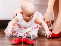 Little girl with red shoes. Lesson of walking. Sweet adorable baby girl making steps at home. Little child toddler wearing princess dress with red small shoes Royalty Free Stock Photo