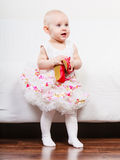 Little girl with red shoes. Lesson of walking. Sweet adorable baby girl making steps at home. Little child toddler wearing princess dress with red small shoes Stock Photography