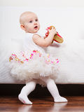Little girl with red shoes. Lesson of walking. Sweet adorable baby girl making steps at home. Little child toddler wearing princess dress with red small shoes Stock Image