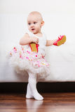 Little girl with red shoes. Lesson of walking. Sweet adorable baby girl making steps at home. Little child toddler wearing princess dress with red small shoes Stock Photos