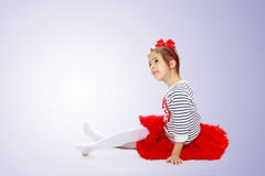 Little girl in a red skirt and bow on her head. Royalty Free Stock Images
