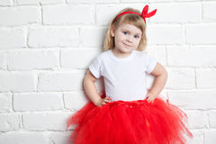 Little girl in a red skirt near a white brick wall Royalty Free Stock Photos