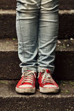 Little girl in red sneakers and jeans standing on the stairs Royalty Free Stock Photo