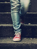 Little girl in red sneakers and jeans standing on the stairs Stock Photo