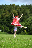 Little girl in a red sundress jumping for joy on the lawn Stock Photos