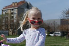 Little girl with red sunglasses stock photo