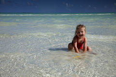Little girl in red swimsuit playing and laughing Stock Photos