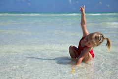 Little girl in red swimsuit playing   in the sea Stock Image