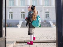 A little girl with red tails in front of the school, looking away. royalty free stock photo