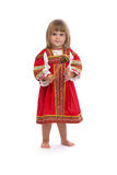 Little girl in red traditional dress with a wooden spoon Royalty Free Stock Image