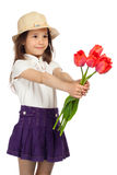 Little girl with red tulips Stock Photography