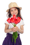Little girl with red tulips Stock Images