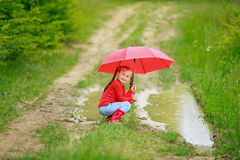 Little girl with red umbrella. Little girl with a red umbrella on the nature Stock Photo
