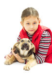 Little girl in a red vest hugs his dog Stock Images