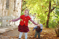 Little girl in red vest throws up leaves Royalty Free Stock Image