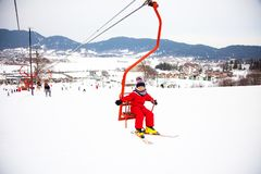Little girl in red winter overall using chairlift in Bakuriani ski resort, Georgia stock photography