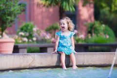 Little girl refreshing in a fountain Stock Photos