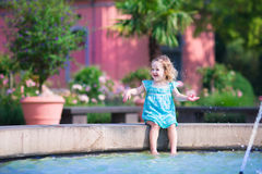 Little girl refreshing in fountain Stock Image