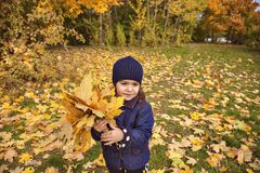 Little girl  rejoices in the colors of autumn.