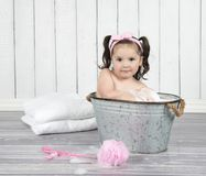Little girl relaxes in bubble bath. Sweet, toddler girl in  pink headband sits in bubble bath in tiny, metal wash tub Royalty Free Stock Photo