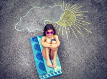 Little girl relaxing on asphalt. Cute creative little girl drawing on asphalt sun and tanning under it, wearing stylish swimsuit and sunglasses, summer holidays royalty free stock photography