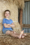Little girl relaxing on bales of hay Royalty Free Stock Image