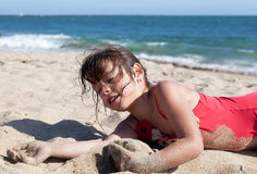 Little Girl Relaxing on the Beach Covered in Sand Stock Photo