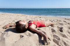 Little Girl Relaxing on the Beach Covered in Sand Royalty Free Stock Photos