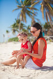 Little girl relaxing on the beach with her young Stock Image