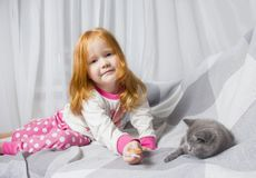 Little girl relaxing on the bed with her kitten. Child is kissing a cat stock images