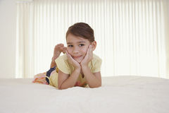 Little Girl Relaxing In Bed. Portrait of happy little girl relaxing with hands on chin in bed Royalty Free Stock Photos