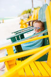 Little girl relaxing in colorful chair at beach Stock Image