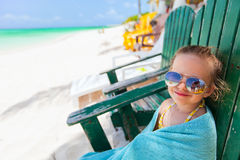 Little girl relaxing in colorful chair at beach Stock Photos