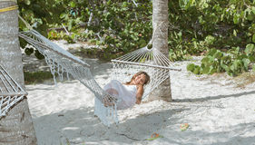 Little girl relaxing at cozy hammock in tropical garden Royalty Free Stock Images