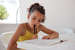 Little girl relaxing with crossword. Child who does crossword puzzles in his spare time Royalty Free Stock Photo
