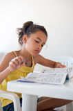 Little girl relaxing with crossword. Child who does crossword puzzles in his spare time Stock Photos