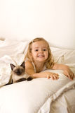Little girl relaxing with her kitten. Little girl relaxing on the bed with her kitten Royalty Free Stock Photos