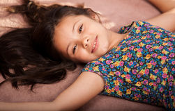 Little girl relaxing at home. Portrait of a cute little girl laying on the carpet and relaxing at home Stock Images