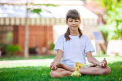Little girl relaxing while sitting on grass. Stock Photos