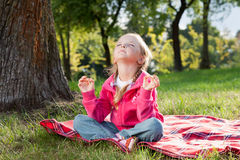 Little girl relaxing in yoga pose on grass Royalty Free Stock Photo