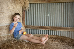 Little girl relzxing on bales of hay in barn Royalty Free Stock Photo