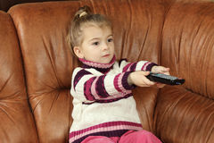 Little girl with remote control in hands. The little girl sits on a sofa with remote control in hands Royalty Free Stock Photography