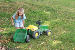 Little girl repairing a tractor Stock Photo
